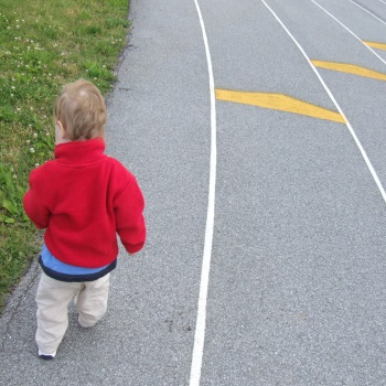 toddler playing on the track at local high school