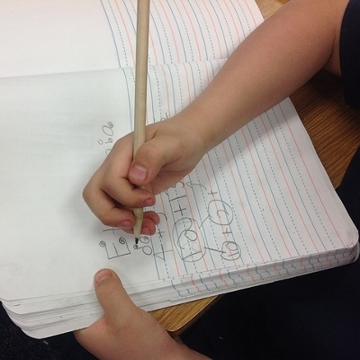 child writing in notebook (400x400)