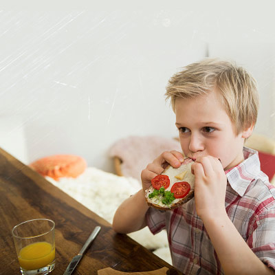 7-8-year-old-eating-a-sandwich-at-home